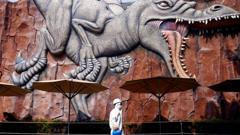 A worker wearing protective suit passing by near a wall where is depicted a dinosaur at Dufan, which is closed amid the coronavirus disease (COVID-19) outbreak spreading in Jakarta