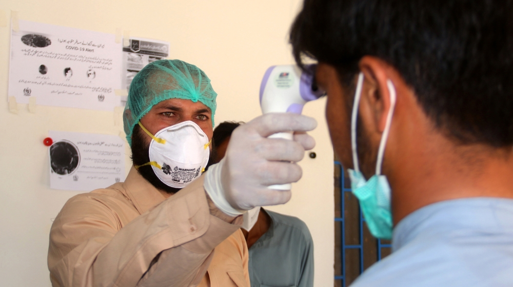 A health worker takes the temperature of a man who returned from Iran and is under medical observation, after Pakistan sealed its border with Iran as a preventive measure following the coronavirus out