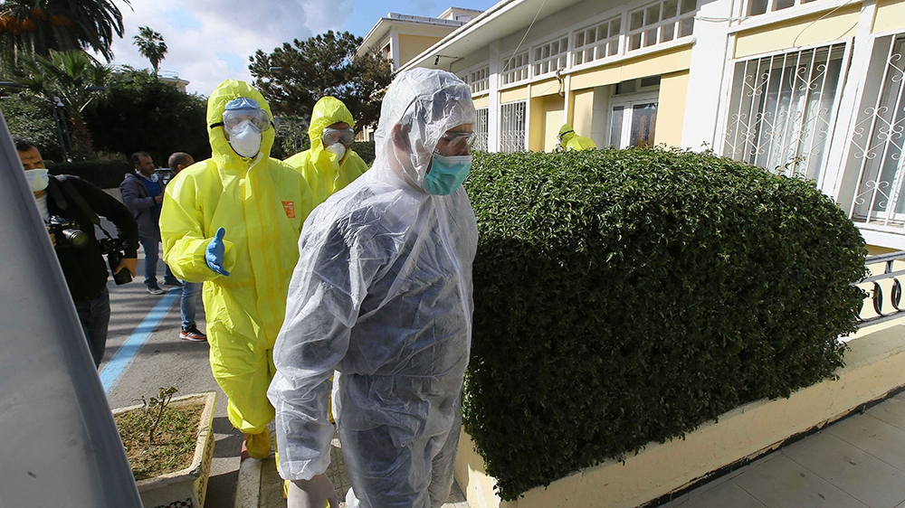 Medics walk outside a clinic where the flight crew as well as several people who were in contact with an Italian man who tested positive for COVID-19 went in for tests, in Algeria, Wednesday, Feb. 26,