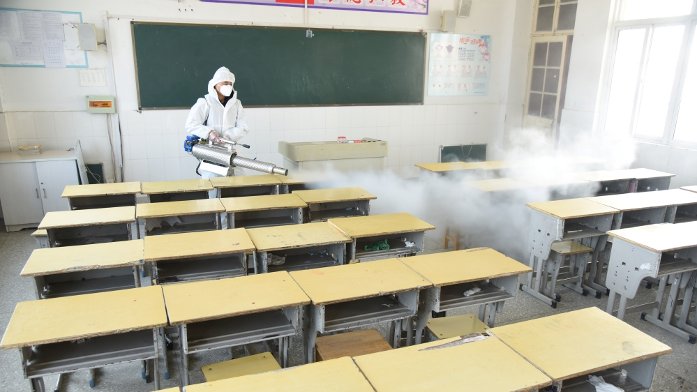Worker in protective suit sprays disinfectant inside a classroom of a primary school, as students' return has been delayed, in Donghai county of Lianyungang, Jiangsu