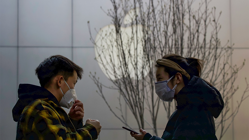 Masked shoppers stand near the Apple logo in Beijing, China. Tech giant Apple has reopened some stores in China but it's stock value has fallen two days in a row as worries grow that the viral outbrea
