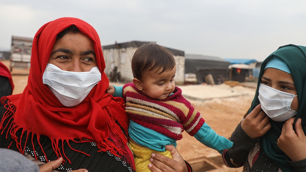 Syrian women wear face masks during an awareness workshop on Coronavirus (COVID-19) held by Doctor Ali Ghazal at a camp for displaced people in Atme town in Syria's northwestern Idlib province, near